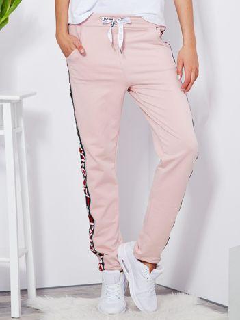 Spodnie dresowe jasnoróżowe z szerokim lampasem