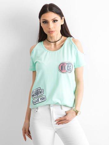 T-shirt miętowy z wycięciami i naszywkami