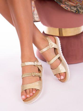Złote sandały z tłoczoną, mieniącą się fakturą na białych podeszwach