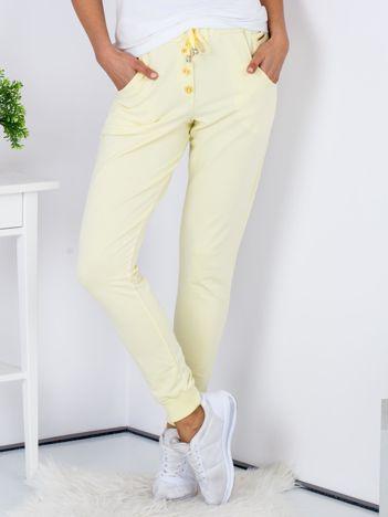 Żółte spodnie dresowe ze złotymi guzikami