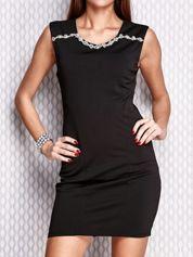 Czarna sukienka z bogatym zdobieniem przy dekolcie
