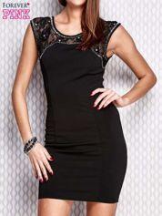 Czarna sukienka z koronkową wstawką i aplikacjami przy dekolcie
