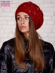 Czerwona czapka z ozdobnym kwiatem i pomponem