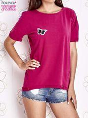 Fuksjowy t-shirt z naszywką motyla i pomponami