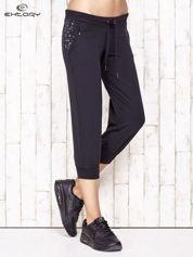 Granatowe spodnie dresowe capri z kwiatowymi kieszeniami