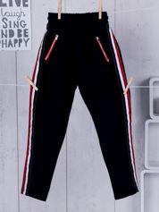 Granatowe spodnie dresowe dla dziewczynki z taśmą tricolor