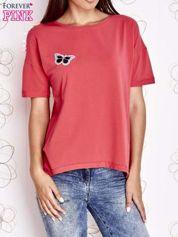 Koralowy t-shirt z naszywką motyla i pomponikami