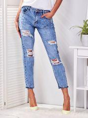 Niebieskie jeansy z przedarciami i perełkami