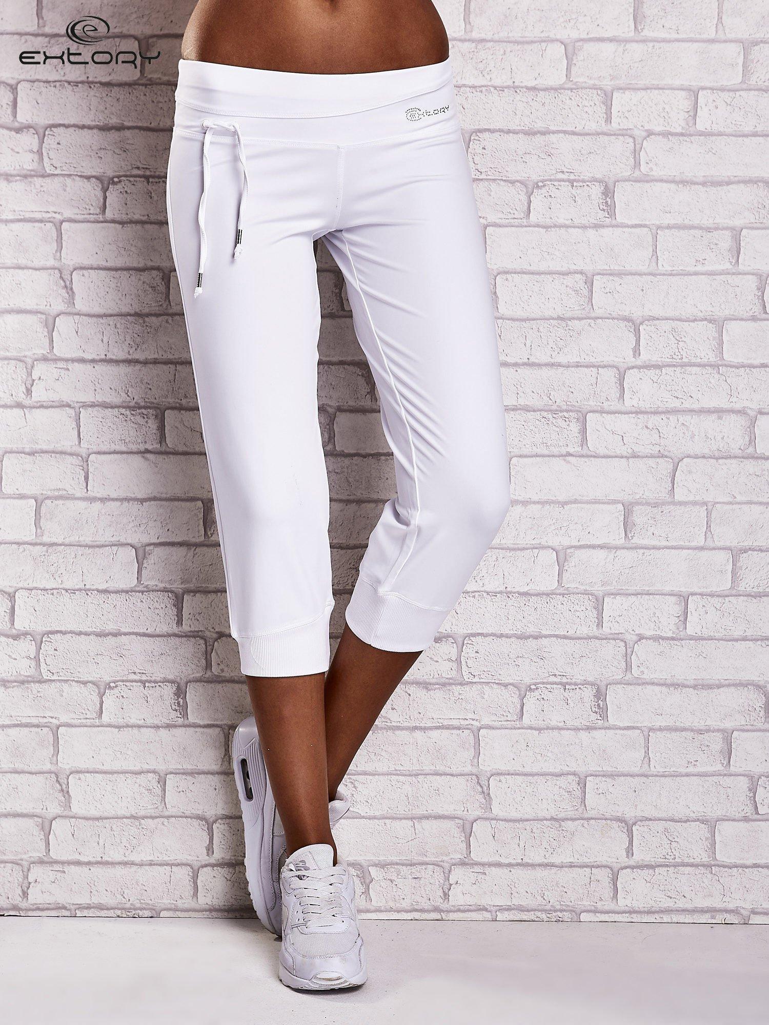Białe śliskie spodnie capri z dżetami i troczkami                                  zdj.                                  1