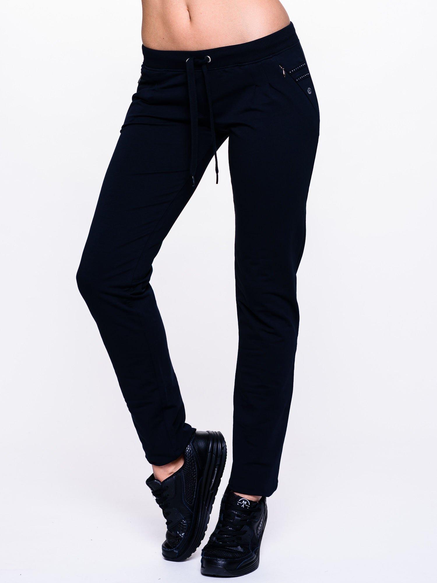 Ciemnogranatowe spodnie dresowe z dżetami przy kieszeniach                                  zdj.                                  1