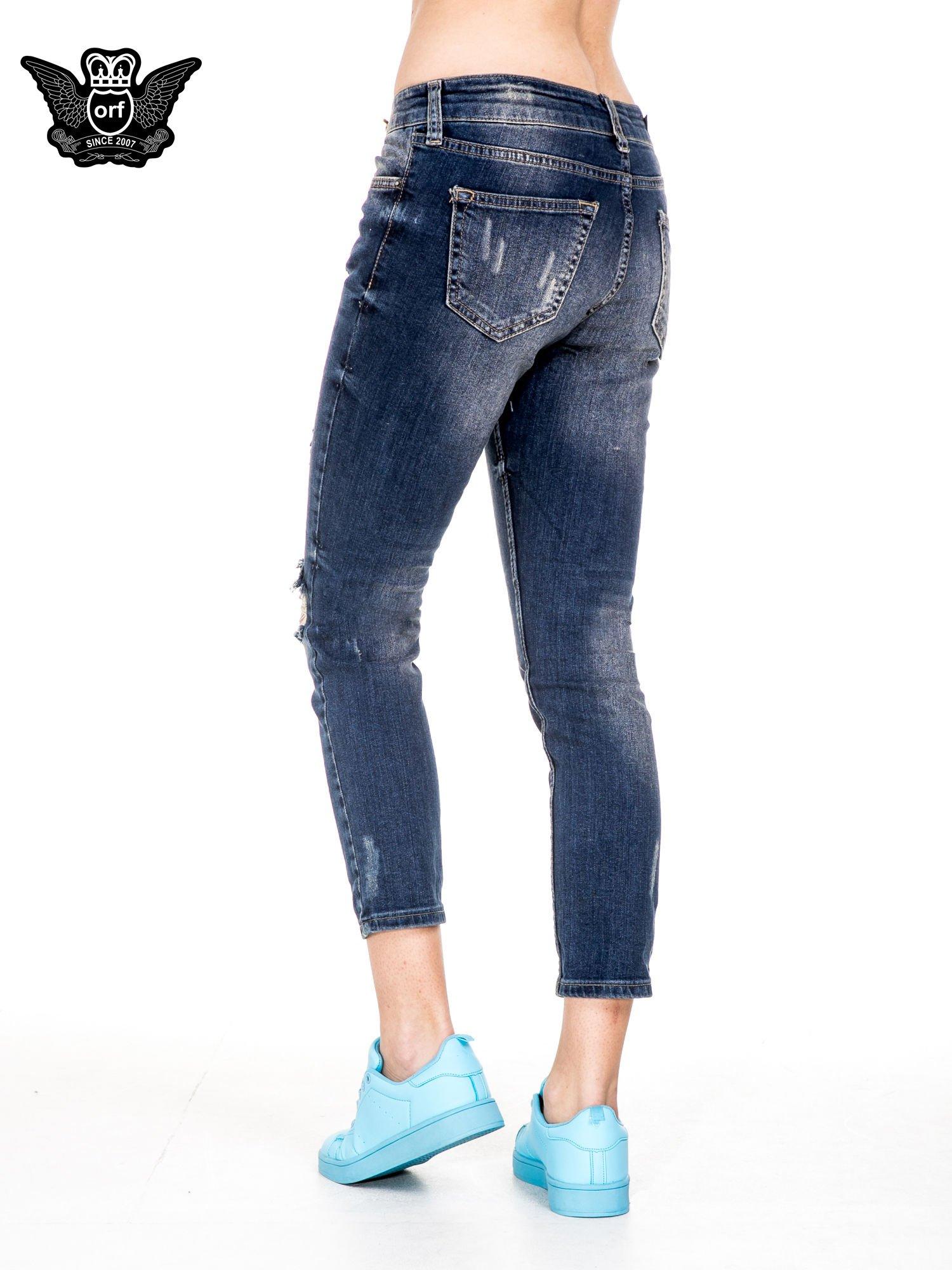 Ciemnoniebieskie spodnie jeansowe rurki z dużymi dziurami                                  zdj.                                  2