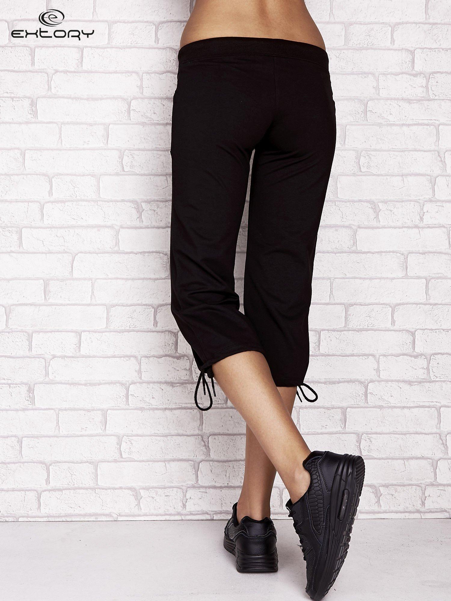 Czarne spodnie dresowe capri z dziewczęcymi nadrukami                                  zdj.                                  2