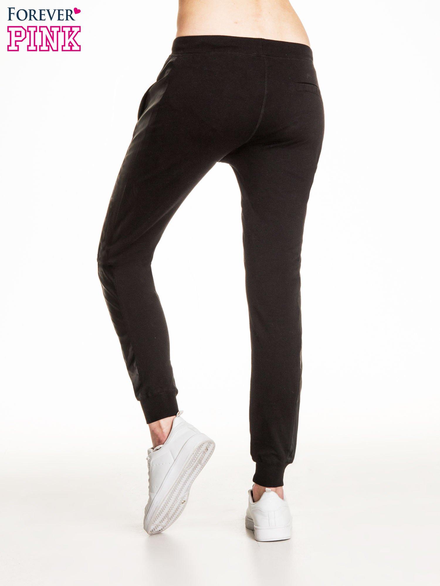 Czarne spodnie dresowe damskie ze skórzanymi lampasami                                  zdj.                                  4