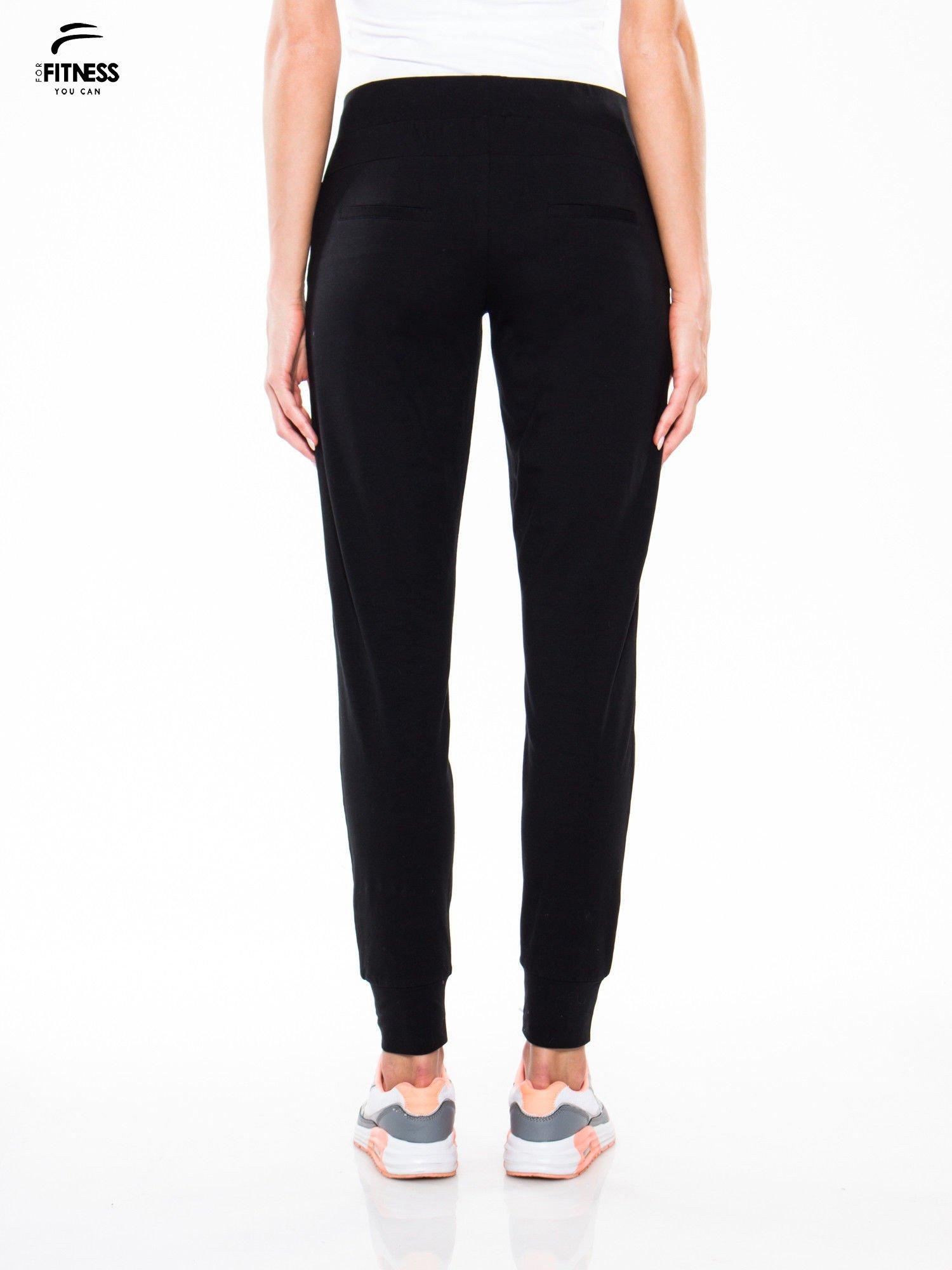 Czarne wąskie spodnie dresowe wiązane w pasie na wstążkę                                  zdj.                                  4