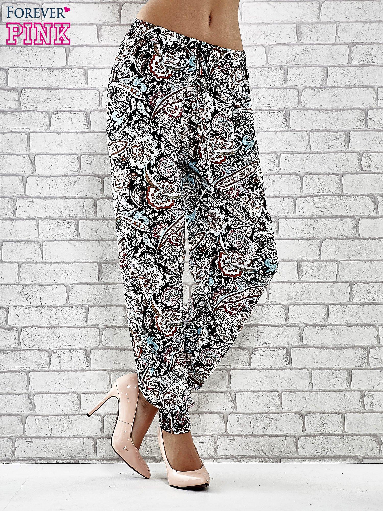 Czarne zwiewne spodnie alladynki we wzór kwiatowy                                  zdj.                                  1