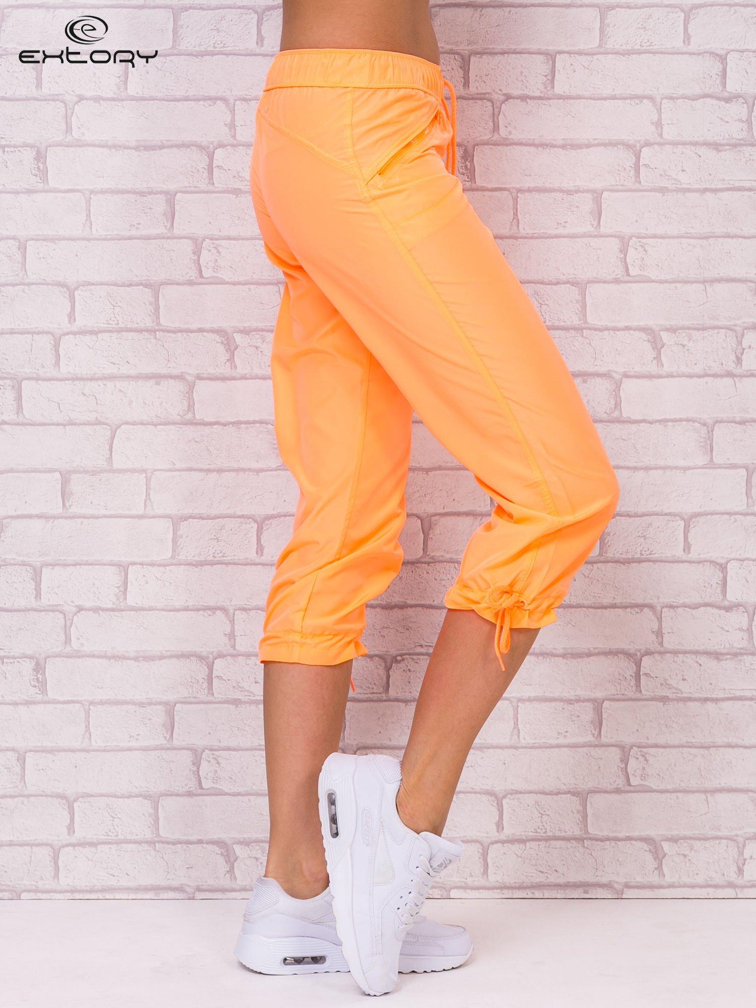Fluopomarańczowe spodnie sportowe capri z wiązaniem                                  zdj.                                  3