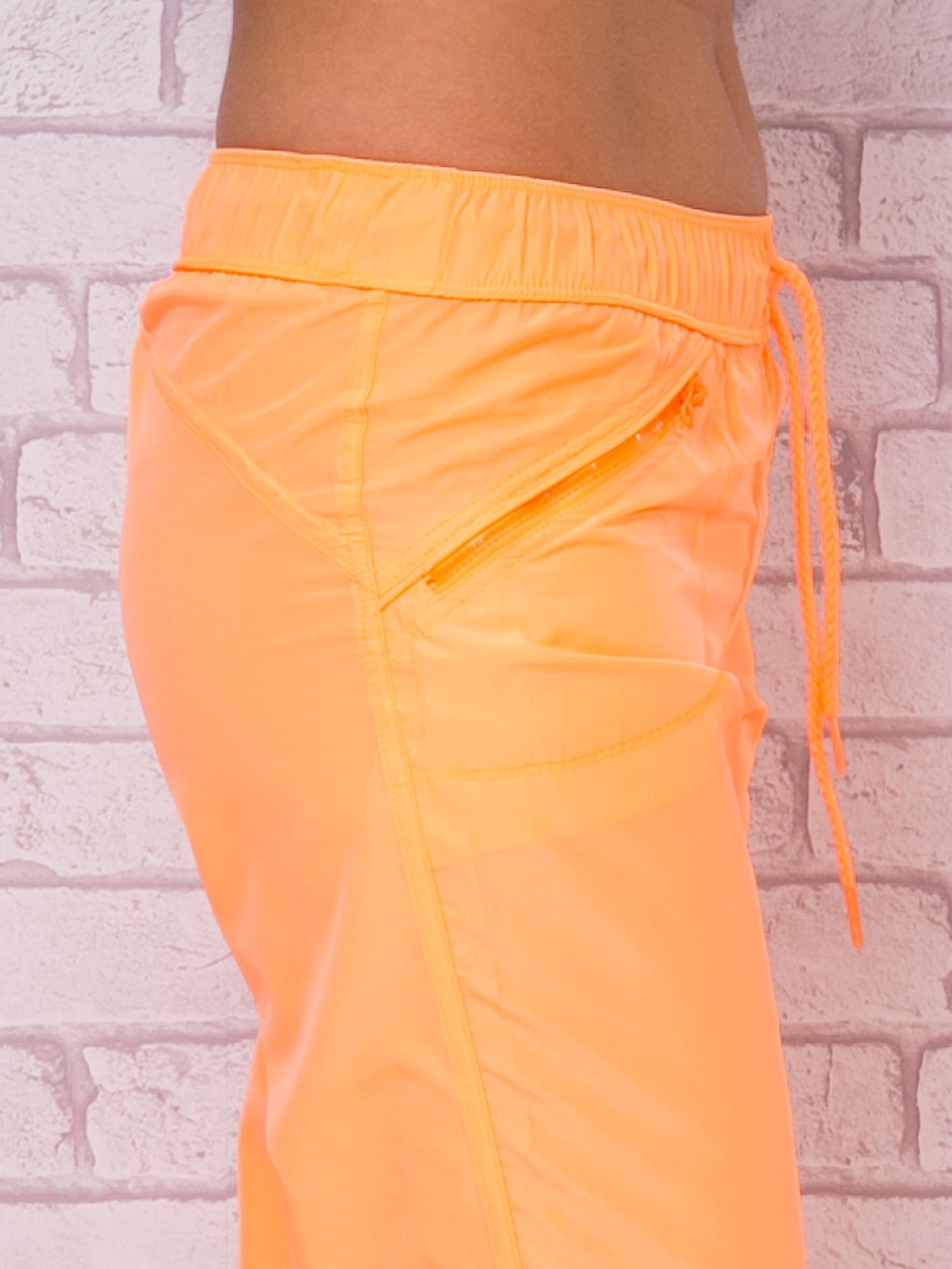 Fluopomarańczowe spodnie sportowe capri z wiązaniem                                  zdj.                                  5