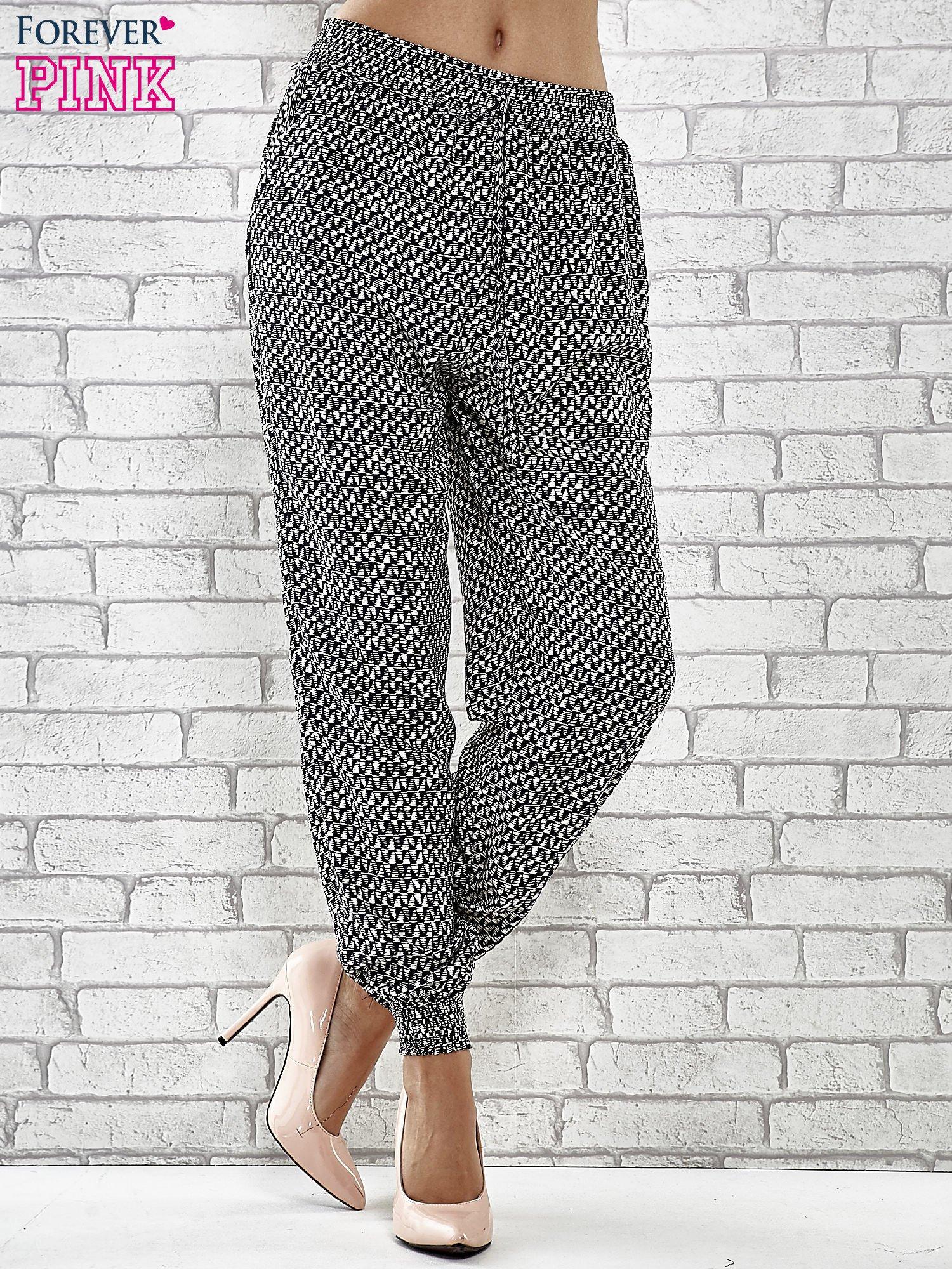 Granatowe zwiewne spodnie alladynki w drobny wzór geometryczny                                  zdj.                                  1