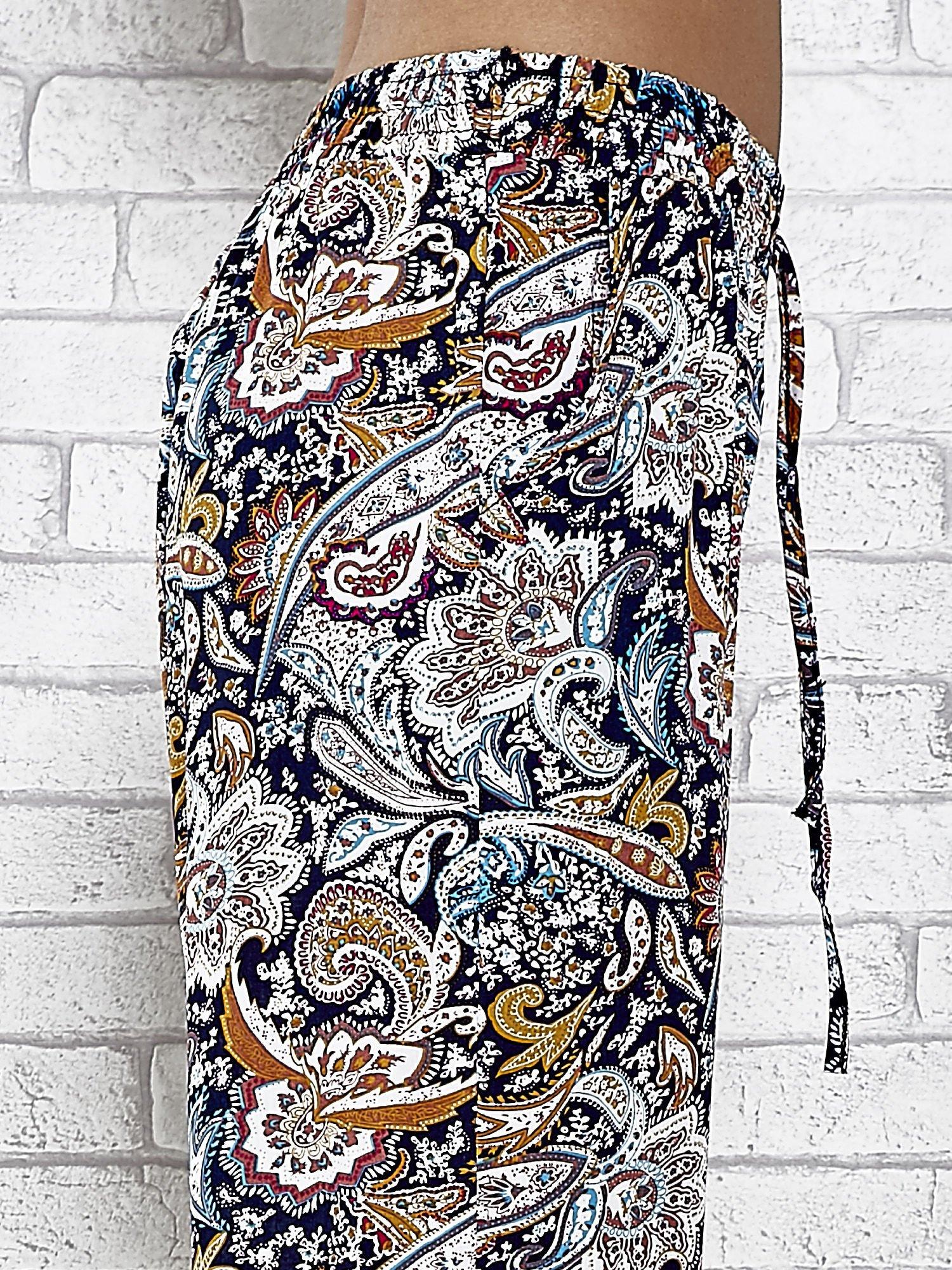 Granatowe zwiewne spodnie alladynki we wzór kwiatowy                                  zdj.                                  6