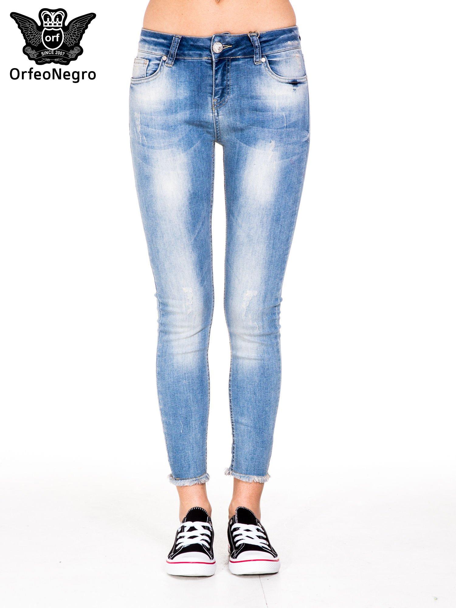 Jasnoniebieskie spodnie jeansowe rurki z poszarpaną nogawką na dole                                  zdj.                                  5
