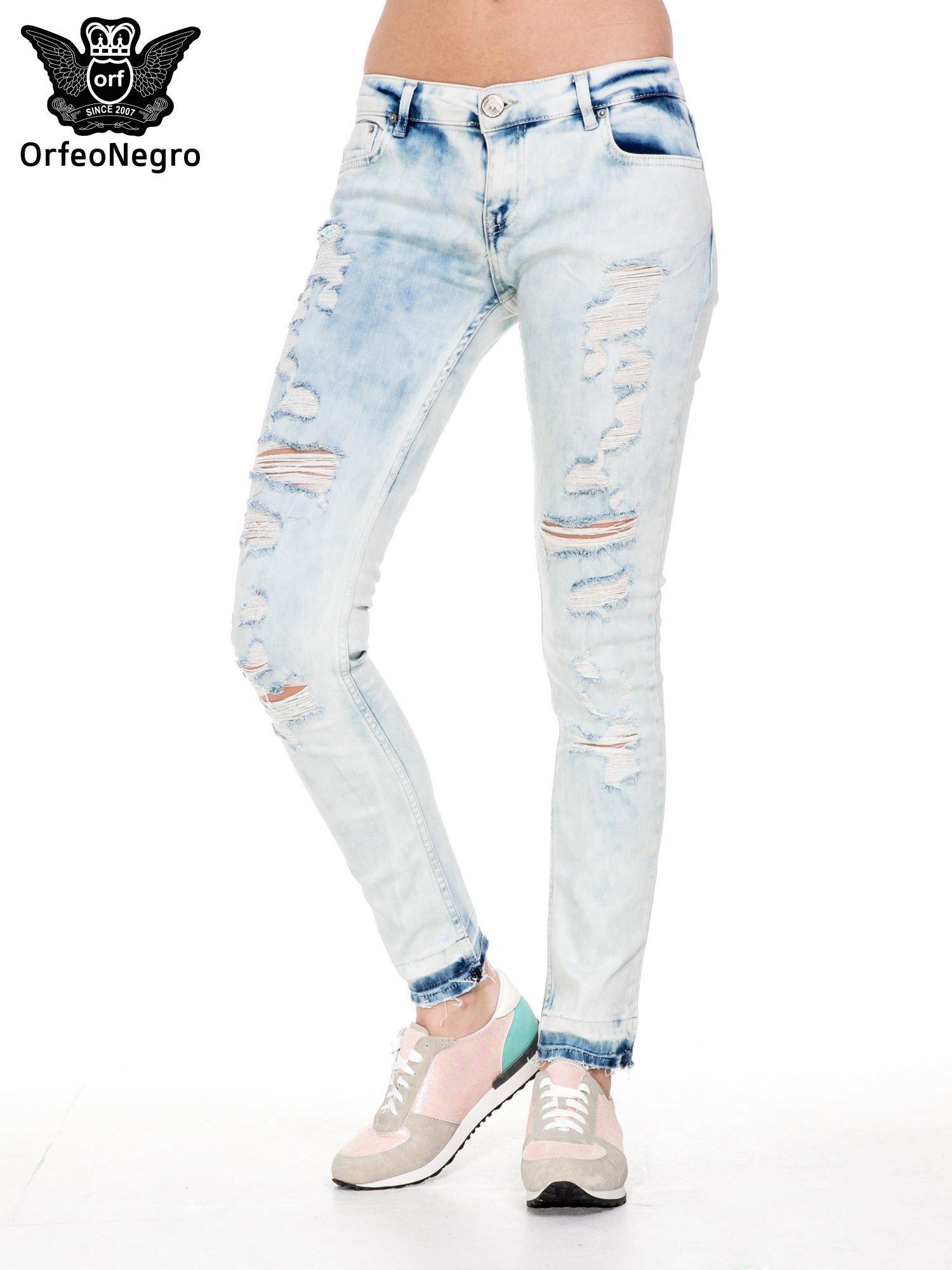 Jasnoniebieskie spodnie jeansowe rurki z przetarciami i poszarpaną na dole nogawką                                  zdj.                                  1