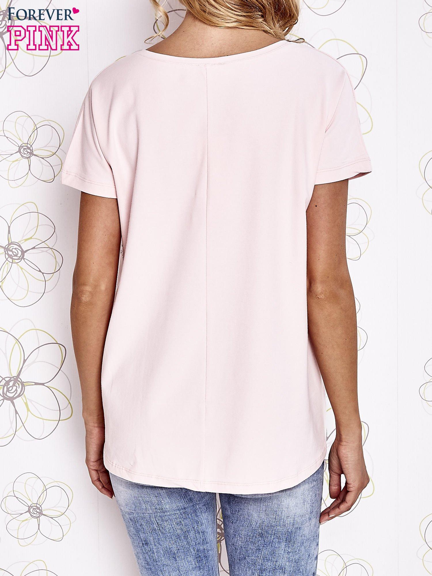 Jasnoróżowy t-shirt z ozdobnym napisem i kokardą                                  zdj.                                  4
