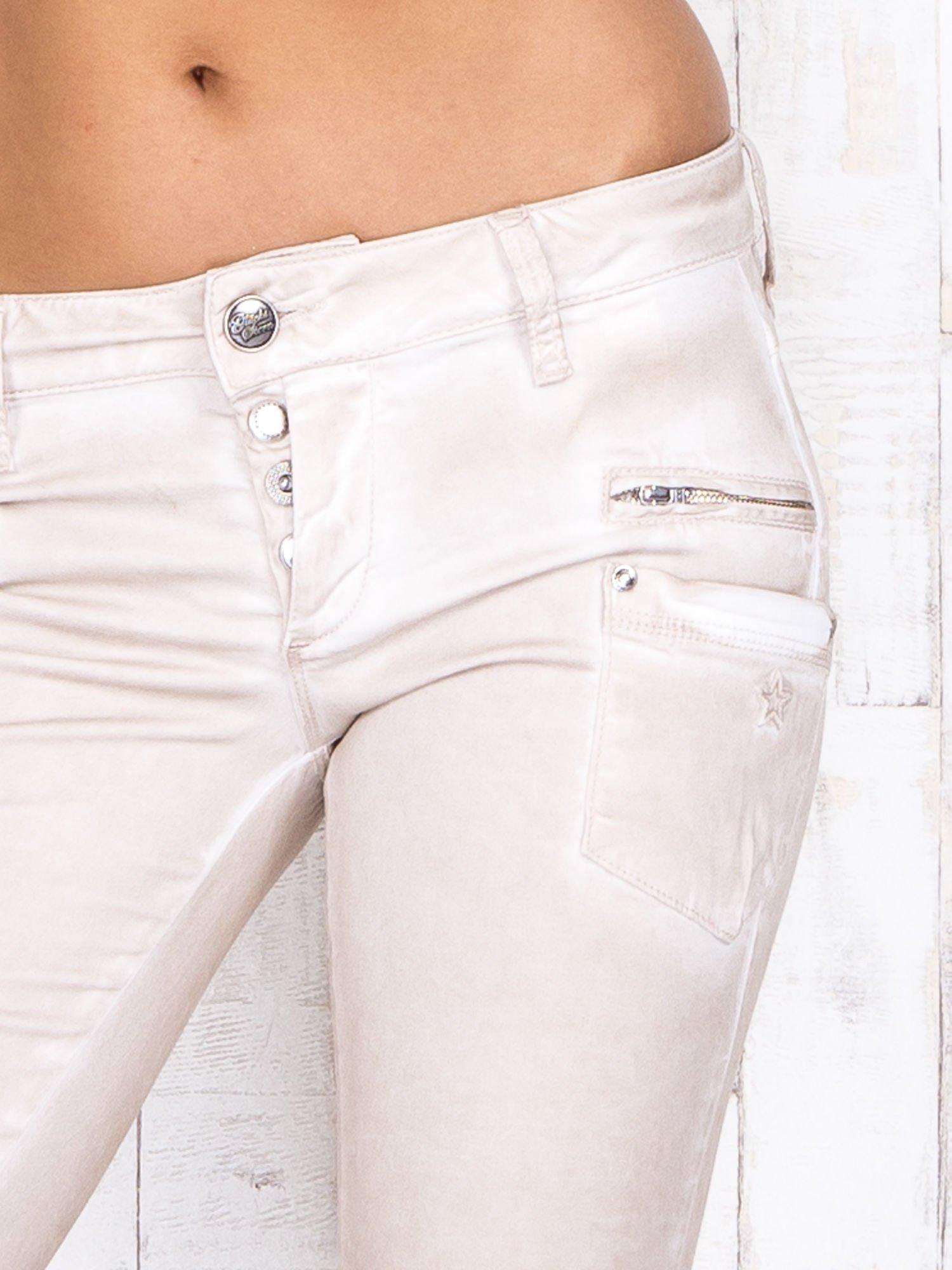 Kremowe materiałowe spodnie skinny z dekatyzacją i suwakami                                  zdj.                                  4