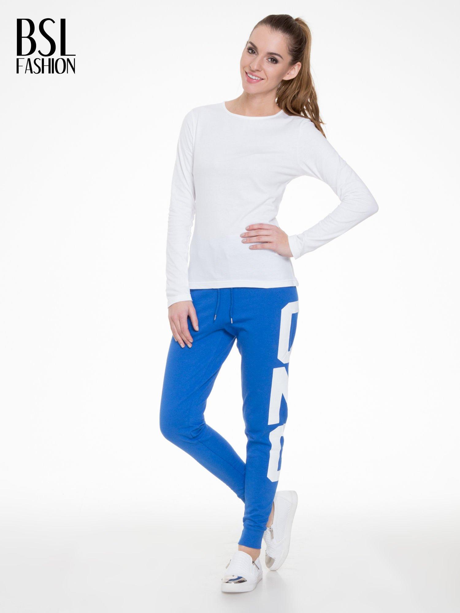 Niebieskie spodnie dresowe z nadrukiem OMG z boku nogawek                                  zdj.                                  2