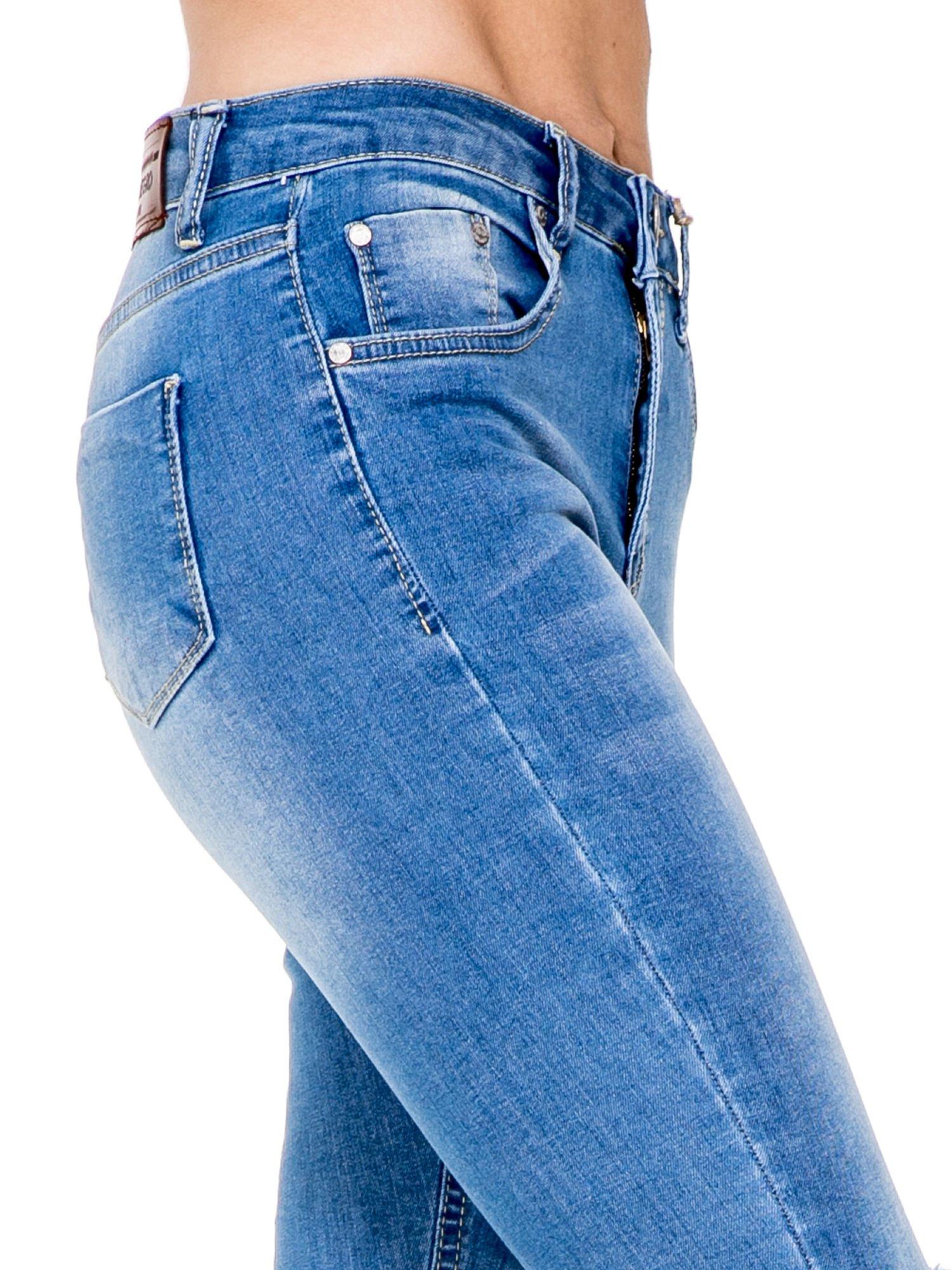 Niebieskie spodnie jeansowe rurki z wysokim stanem i dziurami na kolanach                                  zdj.                                  6