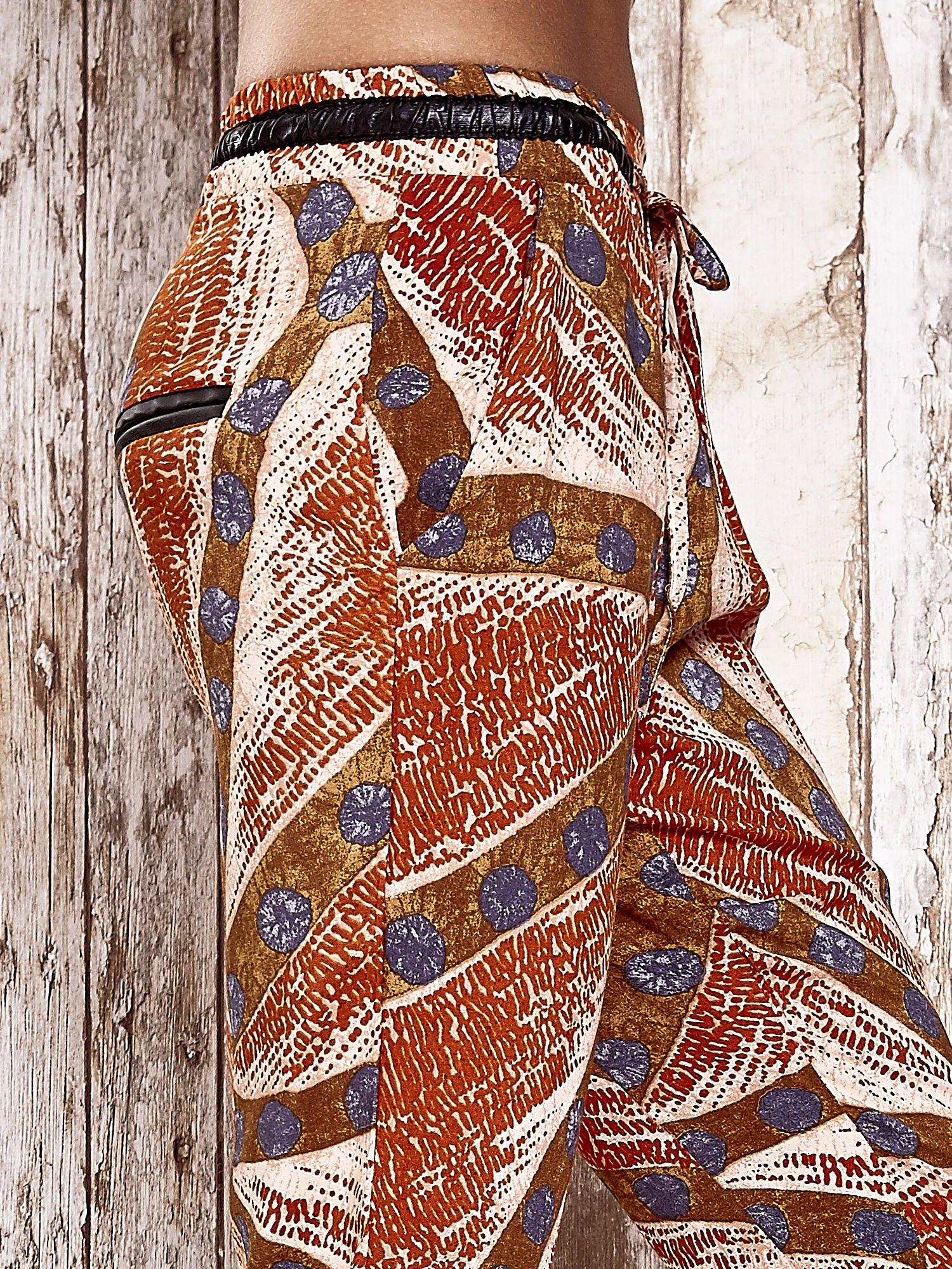 Pomarańczowe lejące spodnie z artystycznym nadrukiem                                  zdj.                                  5