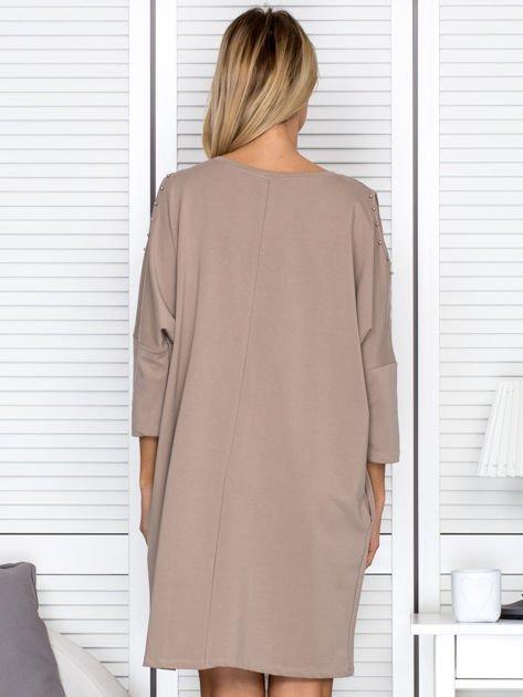 Beżowa sukienka damska oversize z perełkami i okrągłą naszywką                                  zdj.                                  2