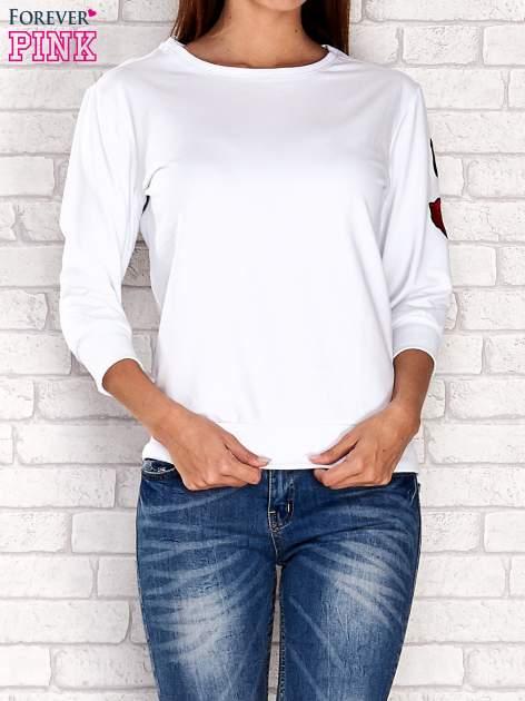 Biała bluza z naszywkami na rękawie
