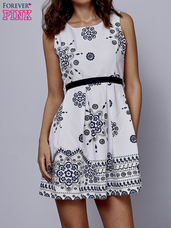 Biała sukienka w ornamenty wiązana na kokardę z tyłu