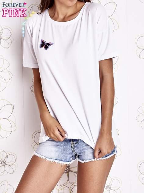 Biały t-shirt z naszywką motyla i pomponami                                  zdj.                                  1