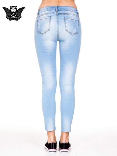 Błękitne spodnie jeansowe rurki z rozdarciam na kolanach                                  zdj.                                  5