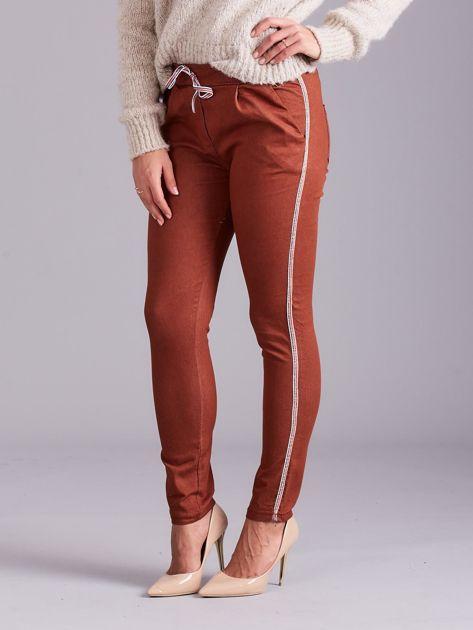 Brązowe spodnie z troczkami i lampasami                              zdj.                              1