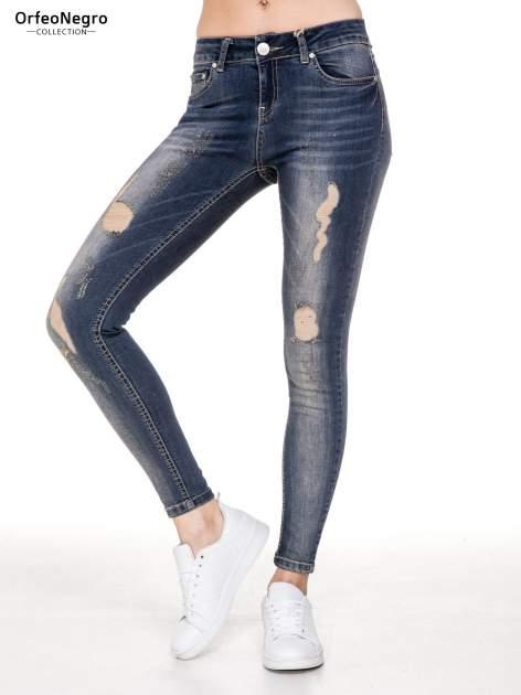 Ciemnoniebieskie rozjaśniane spodnie jeansowe rurki z przetarciami                              zdj.                              1