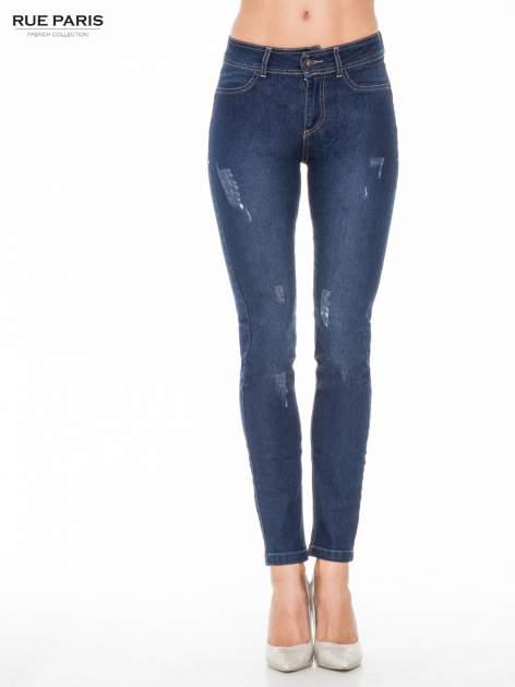 Ciemnoniebieskie spodnie jeansowe rurki z przetarciami                                  zdj.                                  1