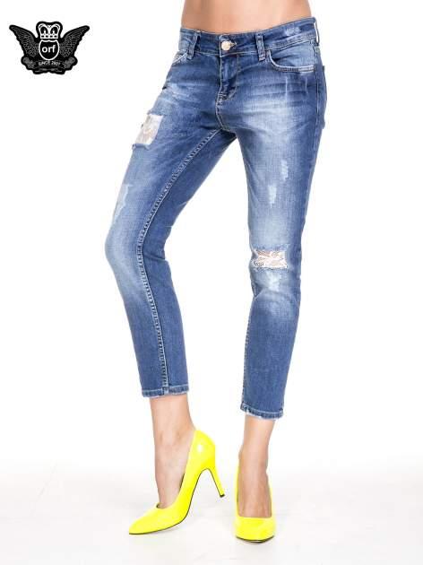 Ciemnoniebieskie spodnie jeansowe z dziurami podszytymi koronką                                  zdj.                                  1