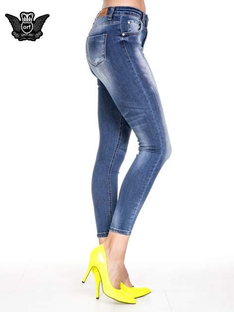 Ciemnoniebieskie spodnie skinny jeans z przecieraną nogawką z przodu                              zdj.                              3