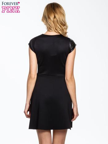 Czarna rozkloszowana sukienka z asymetrycznym wycięciem na dekolcie                                  zdj.                                  4