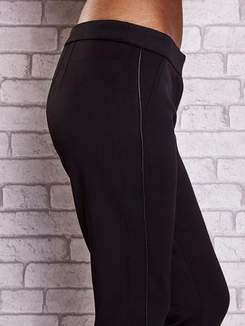 Czarne dopasowane spodnie ze skórzanym prążkiem                                  zdj.                                  5