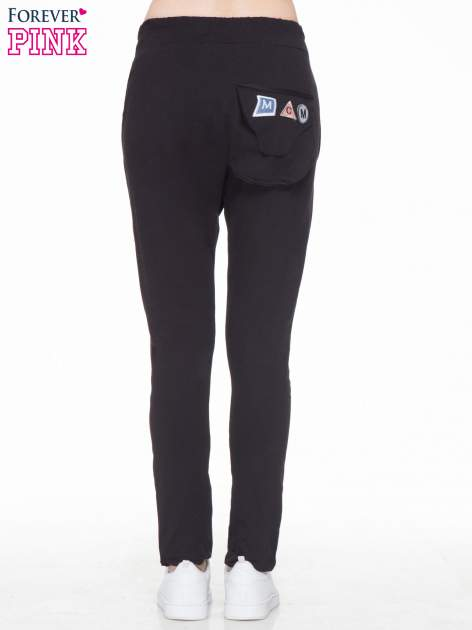 Czarne dresowe spodnie baggy z guzikami i ozdobnymi kieszonkami                                  zdj.                                  2
