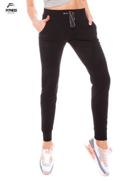 Czarne dresowe spodnie damskie ze ściągaczem i błyszczącym sznurkiem                                  zdj.                                  1
