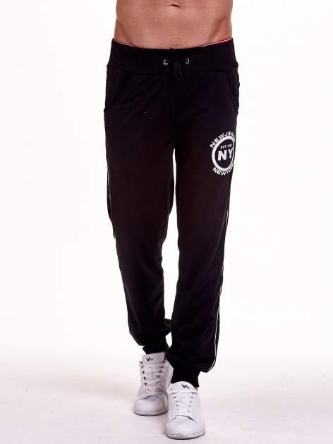 Czarne dresowe spodnie męskie z lampasami po bokach i aplikacją                                  zdj.                                  1