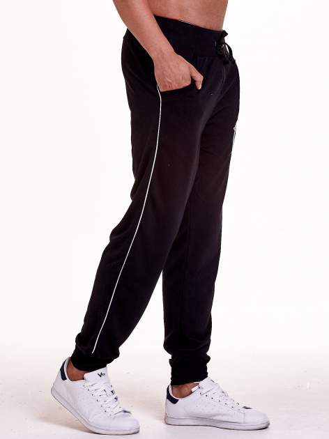 Czarne dresowe spodnie męskie z lampasami po bokach i aplikacją                                  zdj.                                  3