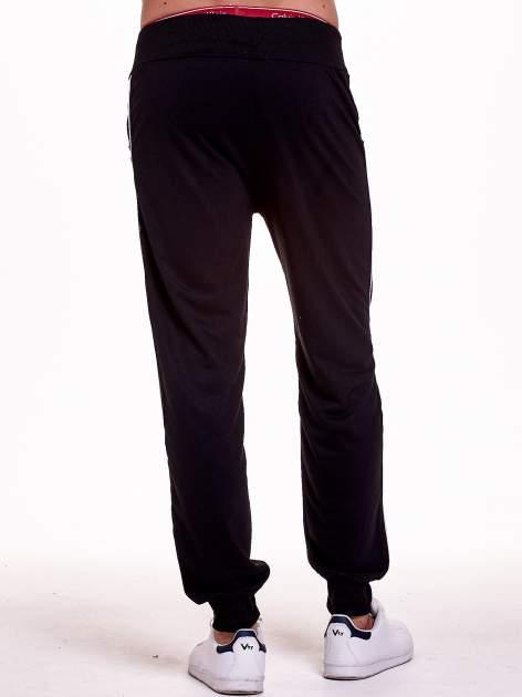 Czarne dresowe spodnie męskie z lampasami po bokach i aplikacją                                  zdj.                                  4