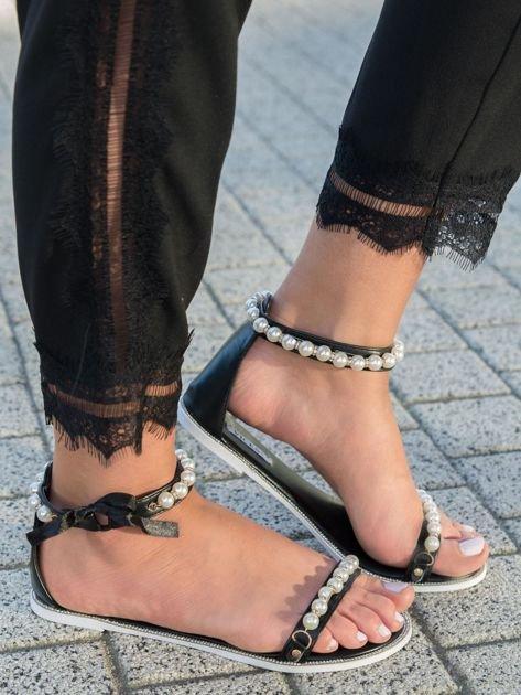 Czarne sandały z ozdobnymi perełkami na przodzie i wokół kostki
