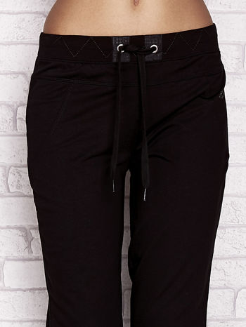 Czarne spodnie dresowe capri z ozdobnym przeszyciem w pasie                                  zdj.                                  4