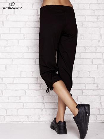 Czarne spodnie dresowe capri z ozdobnym przeszyciem w pasie                                  zdj.                                  2